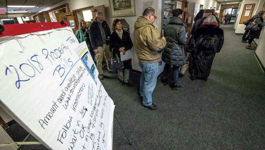Homeowners line up to pay their property taxes to beat the New Year deadline for a tax right off at Town Hall on Friday, Dec 29, 2017, in Bethlehem, N.Y.  (Skip Dickstein/ Times Union) Photo: SKIP DICKSTEIN / 20042530A