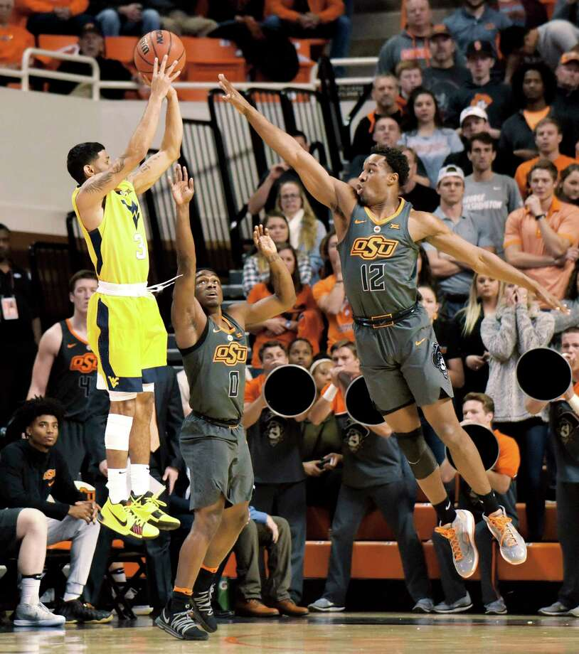 West Virginia guard James Bolden (3) takes a shot at the basket over Oklahoma State defenders guard Brandon Averette (0) and forward Cameron McGriff (12) in the first half of an NCAA college basketball game in Stillwater, Okla., Friday, Dec. 29, 2017. (AP Photo/Brody Schmidt) Photo: Brody Schmidt / FR79308 AP