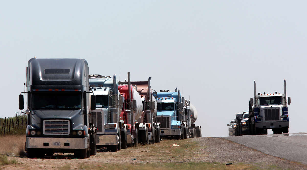 Loaded with fracking sand, trucks wait their turn at a drilling site along State Highway 302 just east of Mentone, Texas, in Loving County, Wednesday, July 25, 2012. With 85 permanent residents, it is the county with the least population in the country. It is augmented with around 1,000 to 1,500 workers that descend on the county during work hours.