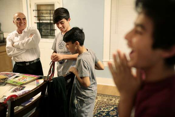 Abdul Nasiri and sons Folad, 14 (left), Tawab, 10, and Sohrab, 12, joke around in their kitchen before dinner in their Oakland home. Nasiri formerly worked as a driver at the U.S. Embassy in Afghanistan.