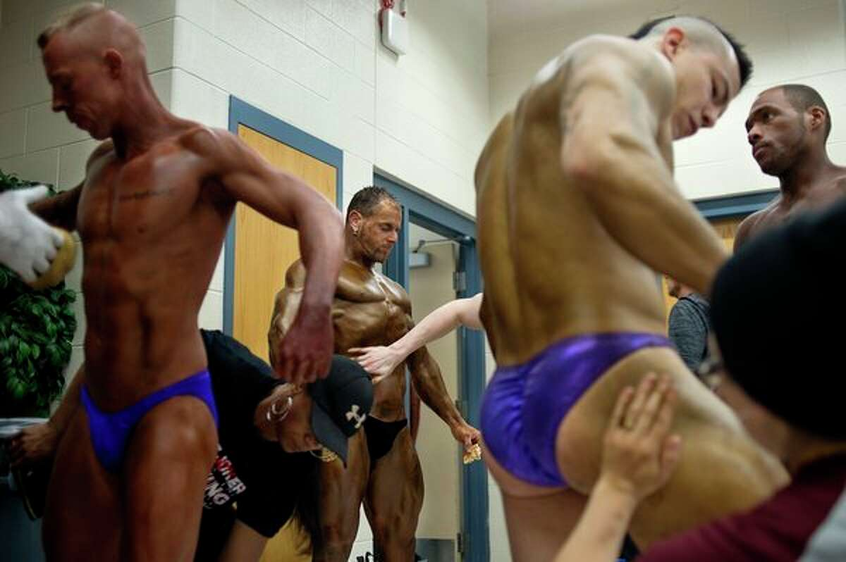 Men competing in the 4th annual ROAR Natural Bodybuilding competition apply tanner before the start of judging on Saturday, April 29 at Bullock Creek High School. (Brittney Lohmiller/Midland Daily News)