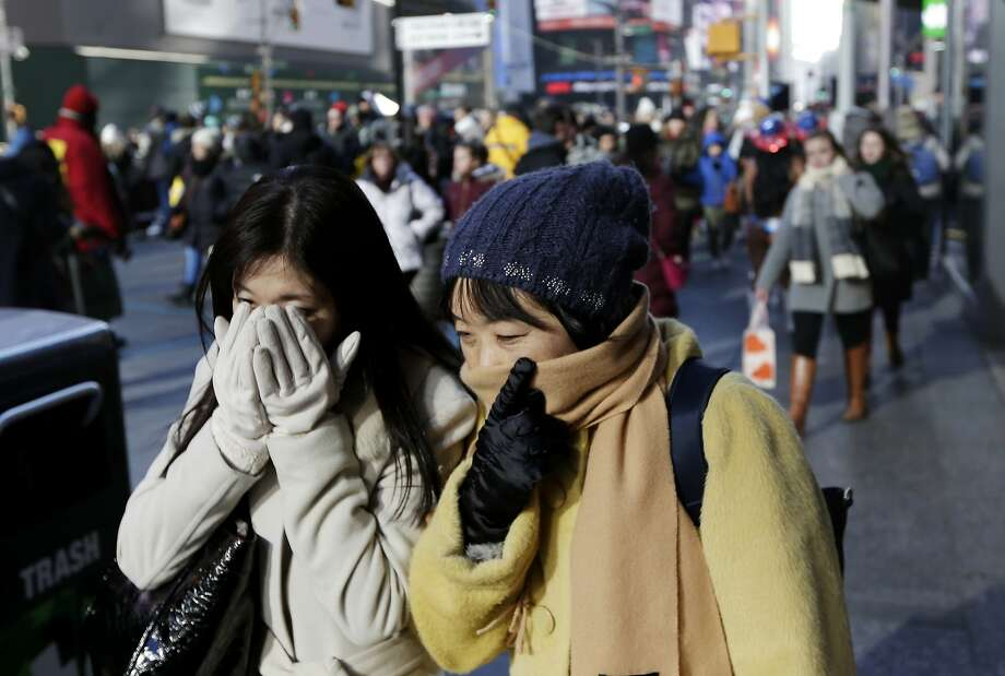 Pedestrians try to keep warm by covering their faces while walking in Times Square, New York, Wednesday, Dec. 27, 2017. Freezing temperatures and below-zero wind chills socked much of the northern United States on Wednesday, and the snow-hardened city of Erie, Pa., dug out from a record snowfall. (AP Photo/Seth Wenig) Photo: Seth Wenig, Associated Press