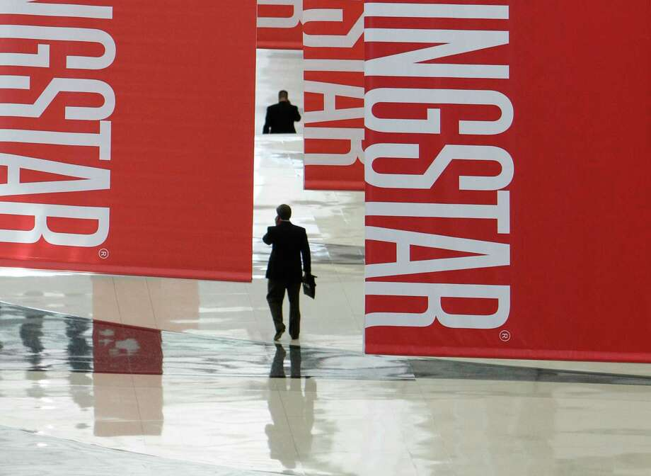 FILE - In this Thursday, June 24, 2010, file photo, attendees of a Morningstar investment conference walk beneath banners at the McCormick Center in Chicago. Understanding mutual fund share classes, and choosing the correct class, could save investors hundreds of thousands of dollars over the long term. (AP Photo/M. Spencer Green, File) Photo: M. Spencer Green / AP2010