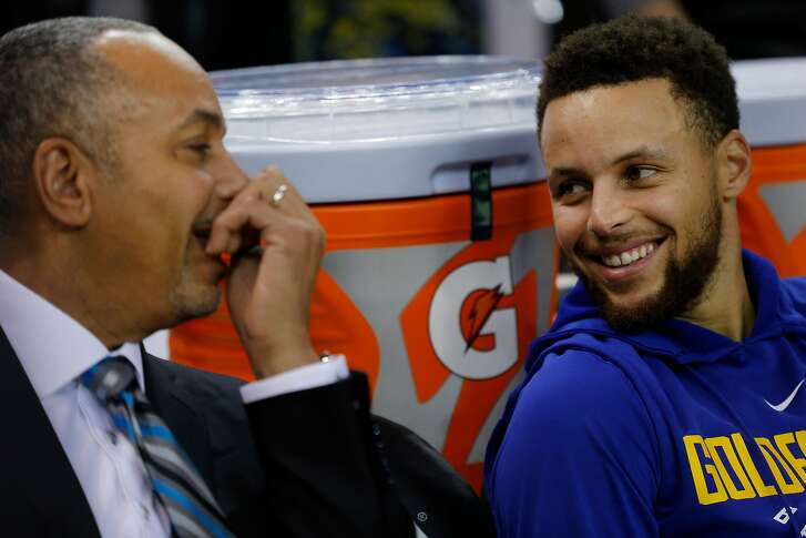Golden State Warriors guard Stephen Curry (30) chats with his father Dell Curry before the start of an NBA basketball game between the Golden State Warriors and Charlotte Hornets at Oracle Arena, Friday, Dec. 29, 2017 in Oakland, Calif. Stephen Curry is recovering from injury and is expected to not play this game.