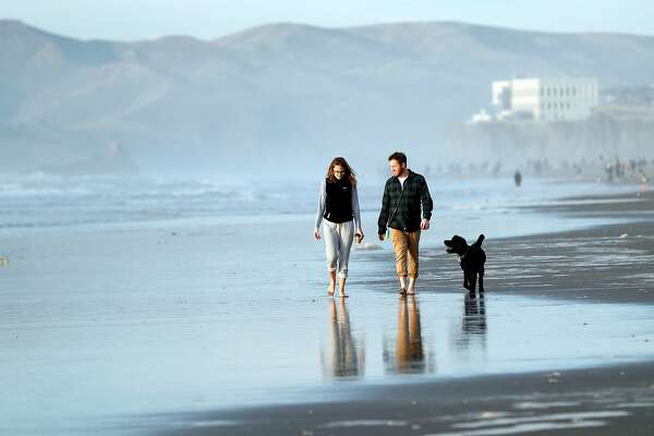Crosby and Callie Branch walk with their dog, Foxy, at Ocean Beach in San Francisco, Calif., on Thursday, December 28, 2017.
