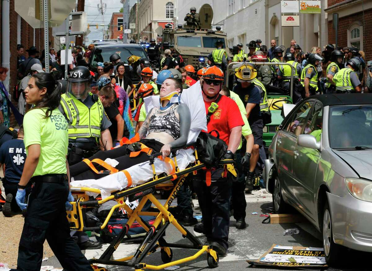 Rescue personnel help injured people after a car ran into a large group of protesters after a white nationalist rally in Charlottesville, Va., in August. The nationalists were protesting plans by the city to remove a statue of Confederate Gen. Robert E. Lee.