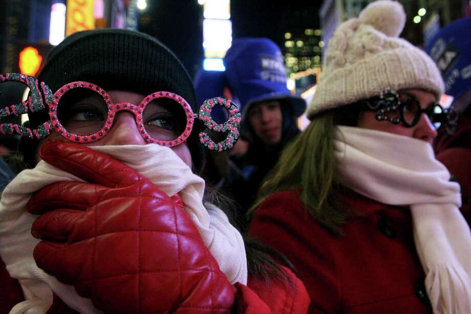 FILE- In this Dec. 31, 2008 file photo, Allison Smith of Jacksonville, Fla, left, tries to keep warm as she and others take part in the New Year's Eve festivities in New York's Times Square. Brutal weather has iced plans for scores of events in the Northeast U.S. from New Year's Eve through New Year's Day, but not in New York City, where people will start gathering in Times Square up to nine hours before the famous ball drop.  (AP Photo/Tina Fineberg, File) Photo: Tina Fineberg / Copyright 2017 The Associated Press. All rights reserved.
