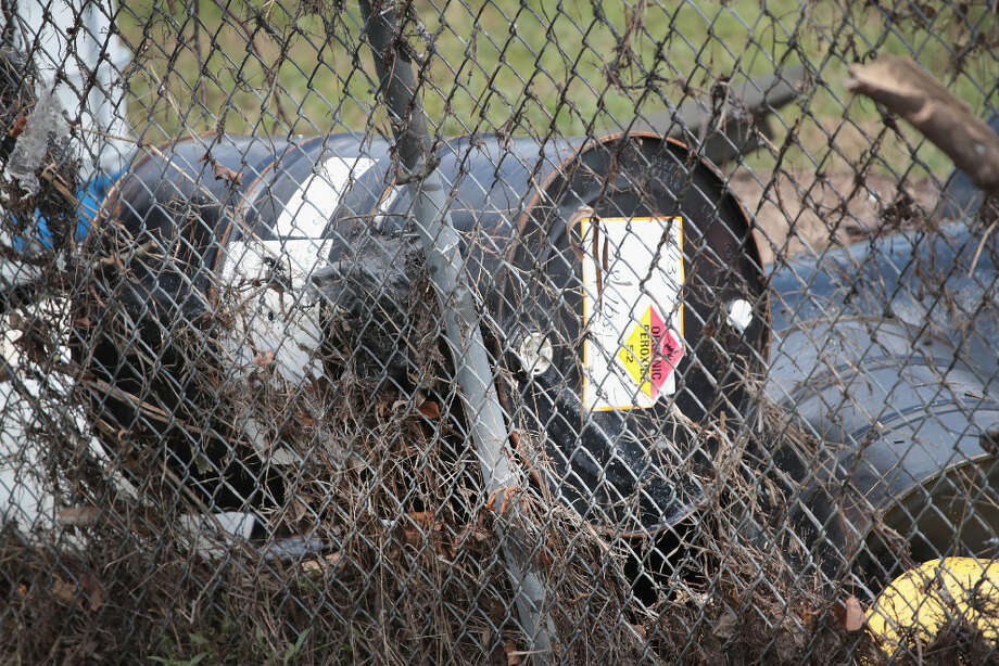 A chemical drum that washed away from the Arkema plant during flooding trapped with other debris by the facilities' border fence in Crosby.