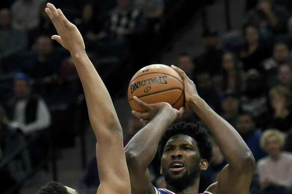 Minnesota Timberwolves center Karl-Anthony Towns (32) guards Philadelphia 76ers center Joel Embiid (21), of Cameroon, during the first quarter of an NBA basketball game on Tuesday, Dec. 12, 2017, in Minneapolis. Towns was called for a foul on the play.