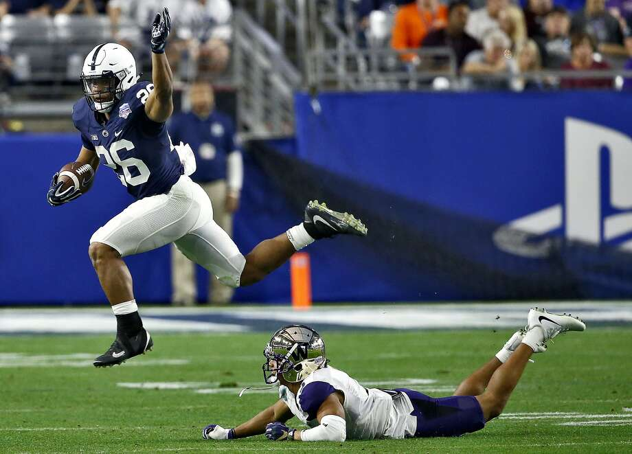 Saquon Barkley, who rushed for 137 yards on 18 carries, leaps over Washington defensive back Myles Bryant during the second half the Penn State's victory in the Fiesta Bowl. Photo: Ross D. Franklin, Associated Press