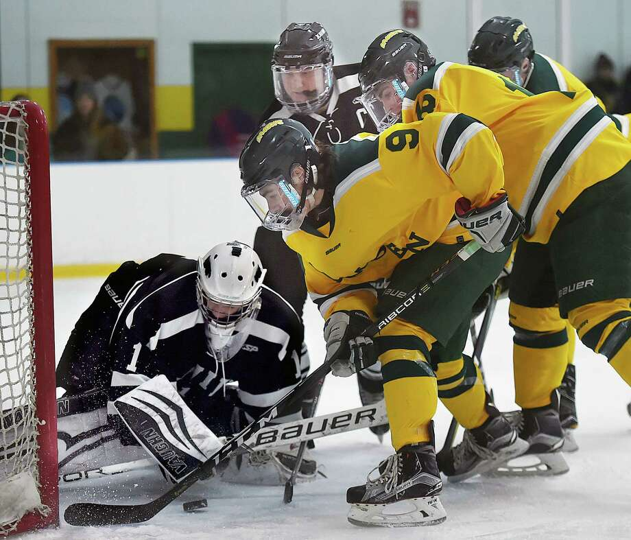 Hamden junior forward Eddy Fracasso (9) and senior captain John Gethings (18) battle Xavier junior goalie Jake Woznyk, Saturday, Dec. 30, 2017, at Astorino Rink in Hamden. Hamden won, 7-4. Photo: Catherine Avalone, Hearst Connecticut Media / New Haven Register