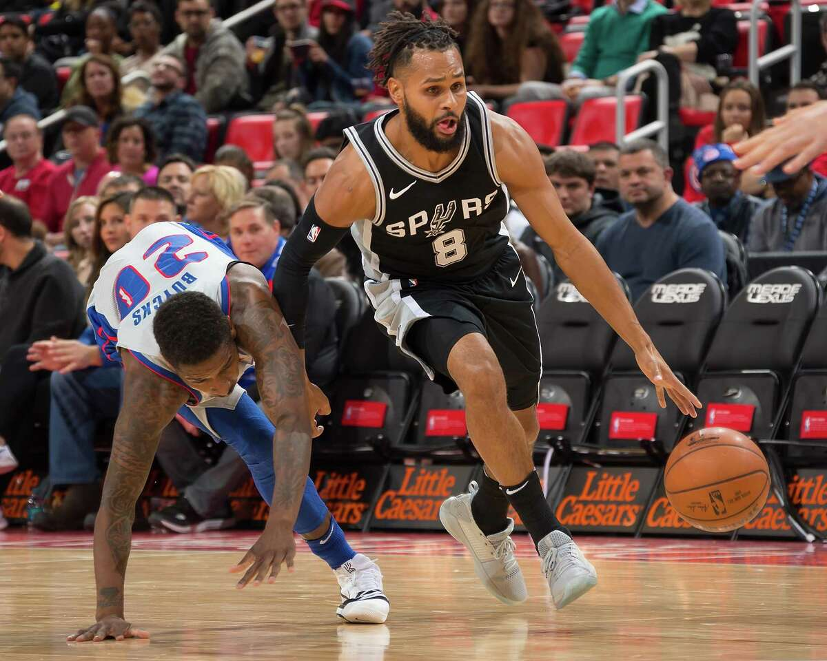 DETROIT, MI - DECEMBER 30: Patty Mills #8 of the San Antonio Spurs drives to the basket past Dwight Buycks #20 of the Detroit Pistons in the first half of an NBA game at Little Caesars Arena on December 30, 2017 in Detroit, Michigan. NOTE TO USER: User expressly acknowledges and agrees that, by downloading and or using this photograph, User is consenting to the terms and conditions of the Getty Images License Agreement.