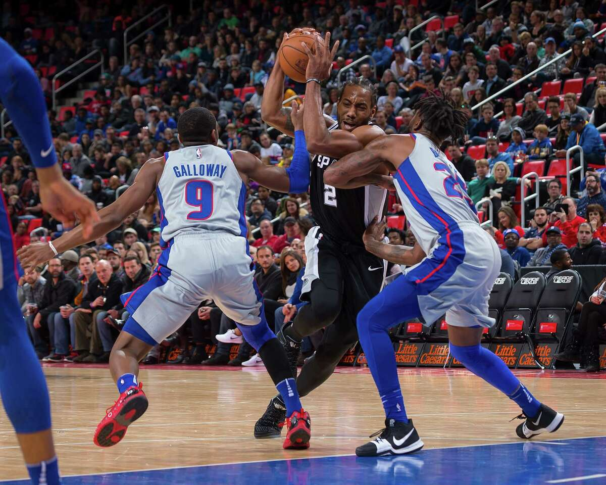DETROIT, MI - DECEMBER 30: Kawhi Leonard #2 of the San Antonio Spurs drives to the basket between Langston Galloway #9 and Reggie Bullock #25 of the Detroit Pistons in the first half of an NBA game at Little Caesars Arena on December 30, 2017 in Detroit, Michigan. NOTE TO USER: User expressly acknowledges and agrees that, by downloading and or using this photograph, User is consenting to the terms and conditions of the Getty Images License Agreement.
