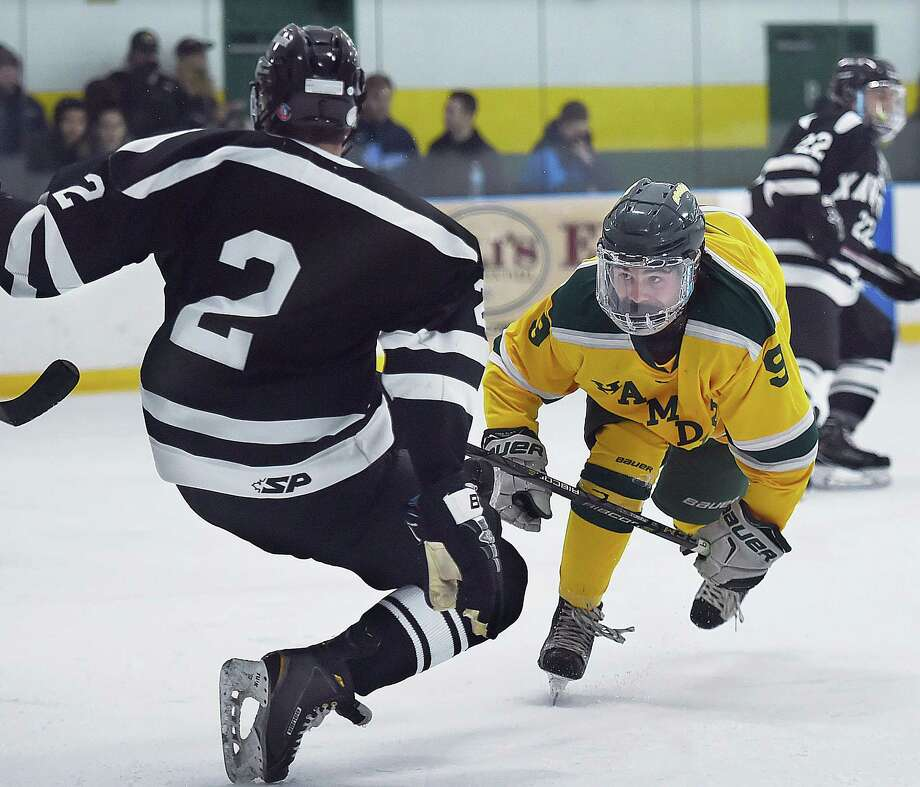 Hamden's Eddy Fracasso maintains control during a collision with Xavier defenseman Luke Lappe on Saturday at Astorino Rink in Hamden. Photo: Catherine Avalone / Hearst Connecticut Media / New Haven Register
