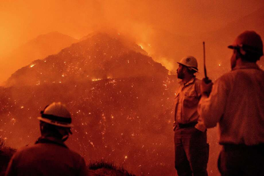 FILE - In this Friday, Dec. 8, 2017 file photo, firefighters monitor the Thomas fire as it burns through Los Padres National Forest near Ojai, Calif. Scientists connect drier weather after heavy rains _ leading to buildup of fuel that can catch fire and burn easily _ to a combination of both man-made warming and a natural La Nina, the climate phenomenon that's the flip side to El Nino, said Georgia Tech climate scientist Kim Cobb. (AP Photo/Noah Berger) Photo: Noah Berger / Noah Berger