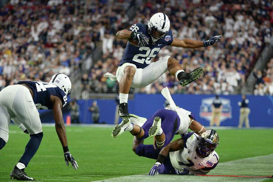 Penn State running back Saquon Barkley leaps over Washington defenders Austin Joyner and Keishawn Bierria in the second half of the Fiesta Bowl. Barkley rushed for 137 yards and two touchdowns. Photo: Jennifer Stewart, Stringer / 2017 Getty Images
