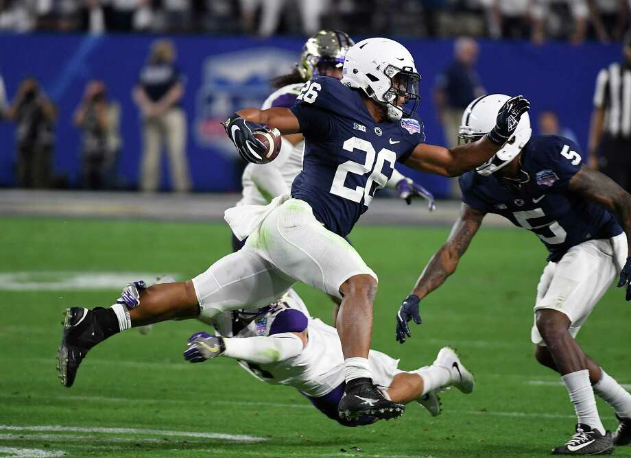 GLENDALE, AZ - DECEMBER 30:  Saquon Barkley #26 of Penn State Nittany Lions leaps over a diving tackle by Taylor Rapp #21 of the Washington Huskies during the second quarter of the Playstation Fiesta Bowl at University of Phoenix Stadium on December 30, 2017 in Glendale, Arizona. Penn State won 35-28. (Photo by Norm Hall/Getty Images) Photo: Norm Hall / 2017 Getty Images
