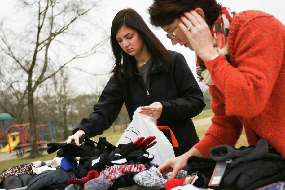 Gabriella Pena, a senior Montgomery County 4-H club member, and her mother Lara Pena, organize cold weather clothing accessories that they are donating to the local homeless on Saturday, Dec. 30, 2017, at Lewis Park in Conroe. Photo: Michael Minasi, Staff Photographer / © 2017 Houston Chronicle