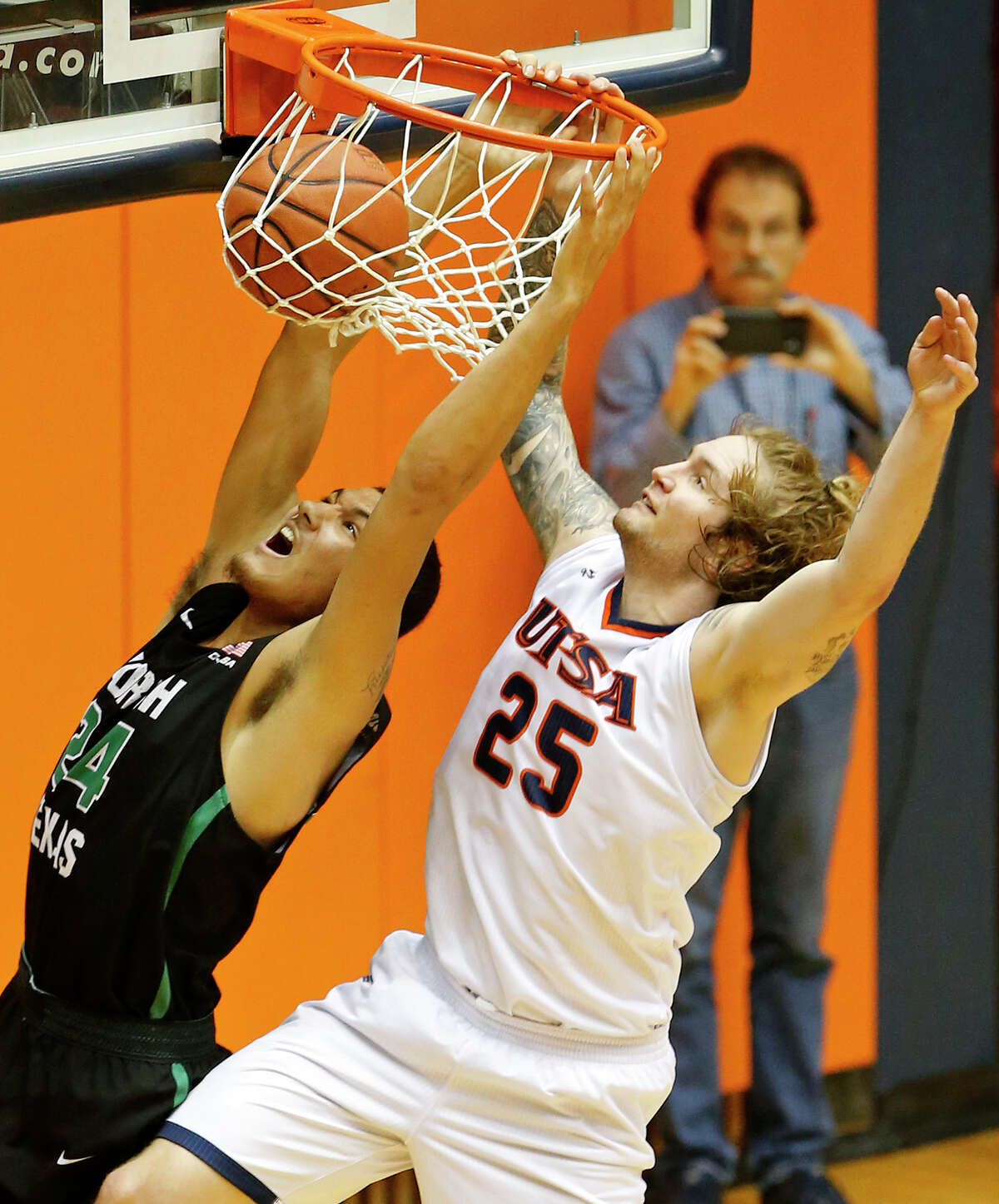 North Texas forward Zachary Simmons (24) dunks around UTSA forward Nick Allen (25) during second half action Saturday Dec. 30, 2017 at the UTSA Convocation Center. North Texas won 72-71.