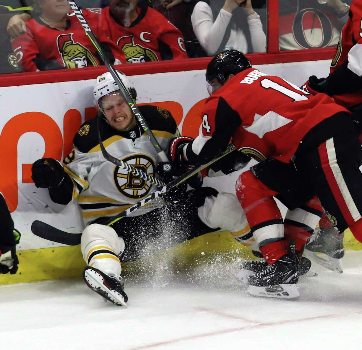 Boston Bruins' David Pastrnak (88) reacts after being checked by Ottawa Senators' Alexandre Burrows (14) during the third period of an NHL hockey game Saturday, Dec. 30, 2017, in Ottawa, Ontario. (Fred Chartrand/The Canadian Press via AP)