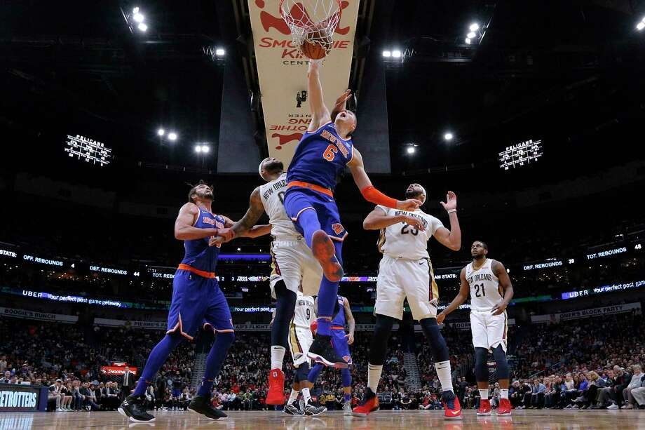 New York Knicks forward Kristaps Porzingis (6) dunks over New Orleans Pelicans forward Anthony Davis (23) and center DeMarcus Cousins (0) during the second half of an NBA basketball game in New Orleans, Saturday, Dec. 30, 2017. The Knicks won 105-103. (AP Photo/Jonathan Bachman) Photo: Jonathan Bachman / FR170615 AP
