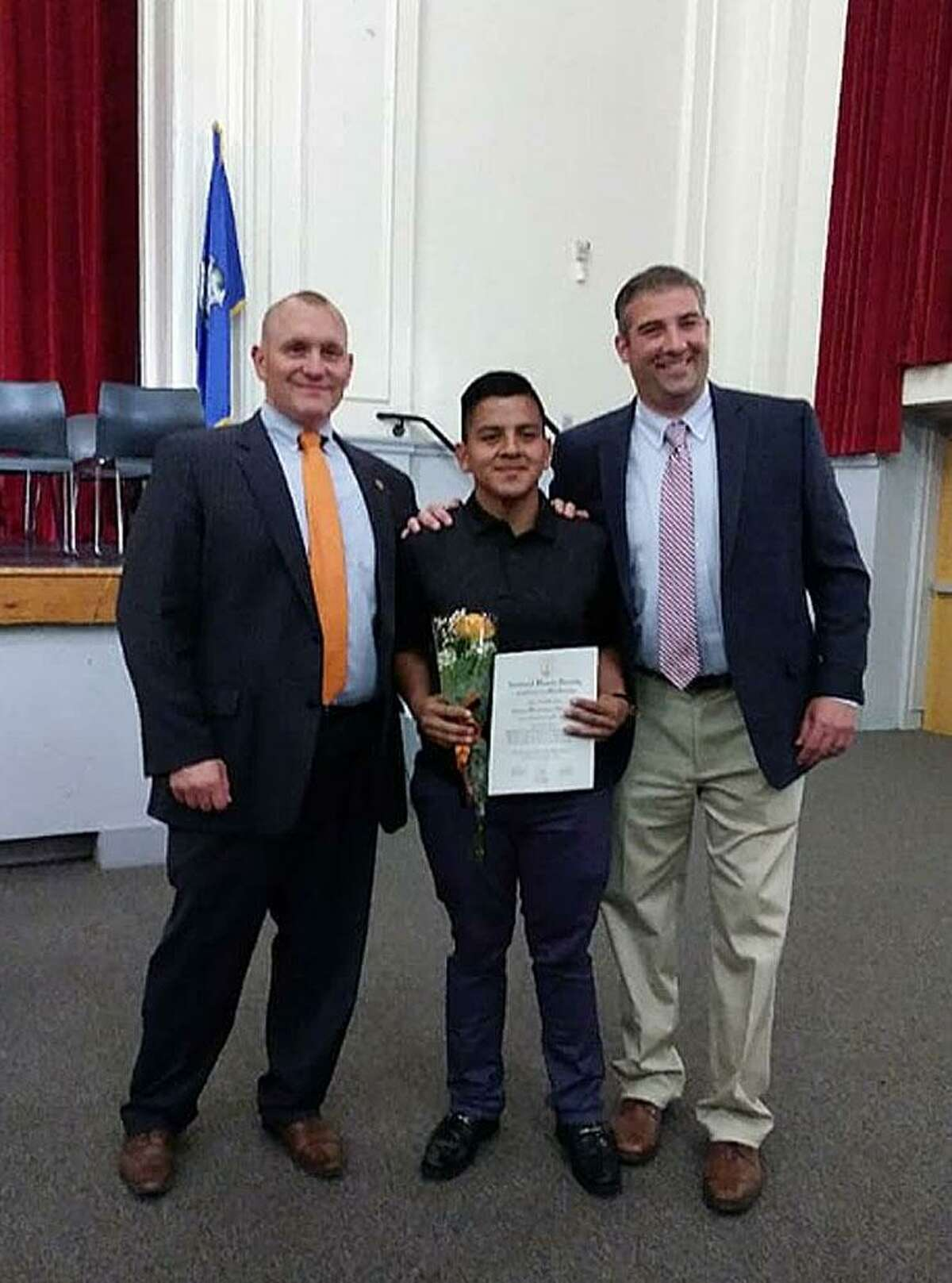 Erwin Hernandez, center, is recognized by Stamford High Principal Ray Manka, left, and Assistant Principal Matt Forker after being inducted into the National Honor Society. Hernandez had his leg amputated after an accident last week.
