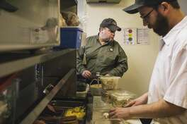 PORTLAND, ME - MARCH 13: Food safety inspector Tom Williams looks at food storage as Becky's line cook Michael Sajecki slices mushrooms for omelets at Becky's Diner in Portland, ME on Friday, March 13, 2015. (Photo by Whitney Hayward/Portland Press Herald via Getty Images)