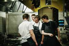 Executive chef and kitchen staff discussing food preparation in restaurant kitchen