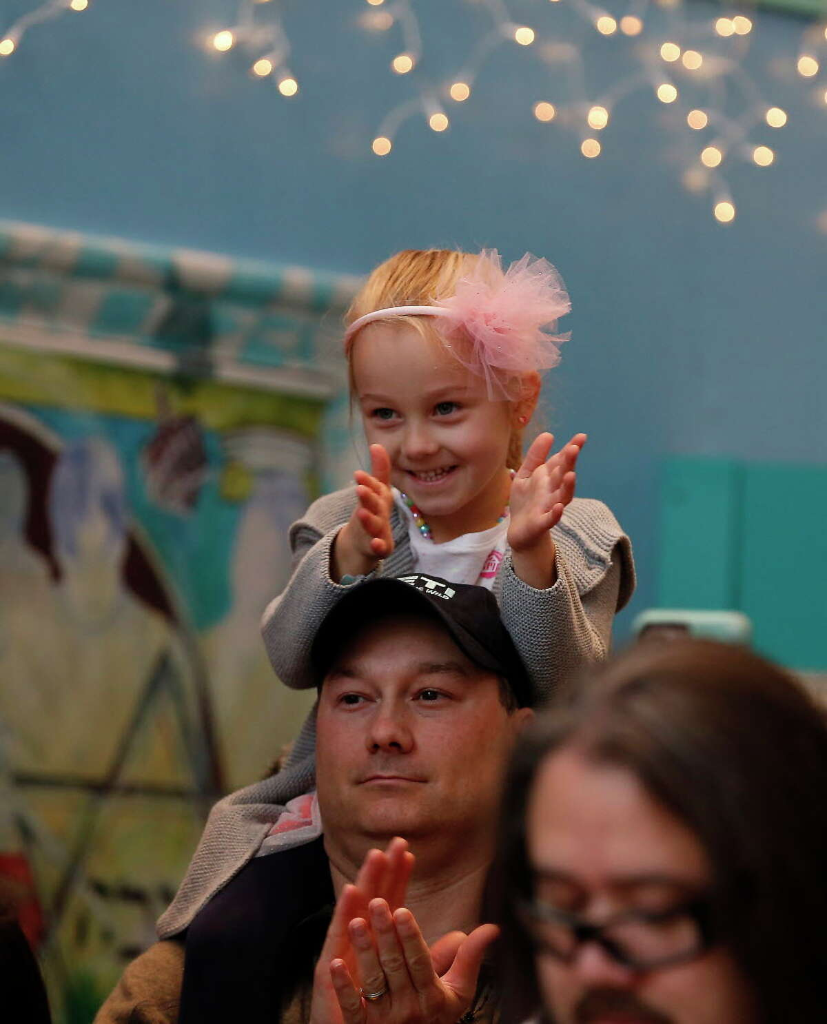 Elizabeth Baudin, 4, enjoys the view from her father's, Brandon, shoulders during The Children's Museum of Houston's Rockin' New Year's Noon Bash Sunday, Dec. 31, 2017, in Houston. The event is the city's longest-running New Year's Eve celebration just for kids. This end-of-year bash rings in the New Year at the stroke of noon with a parade and shimmering ball drop.