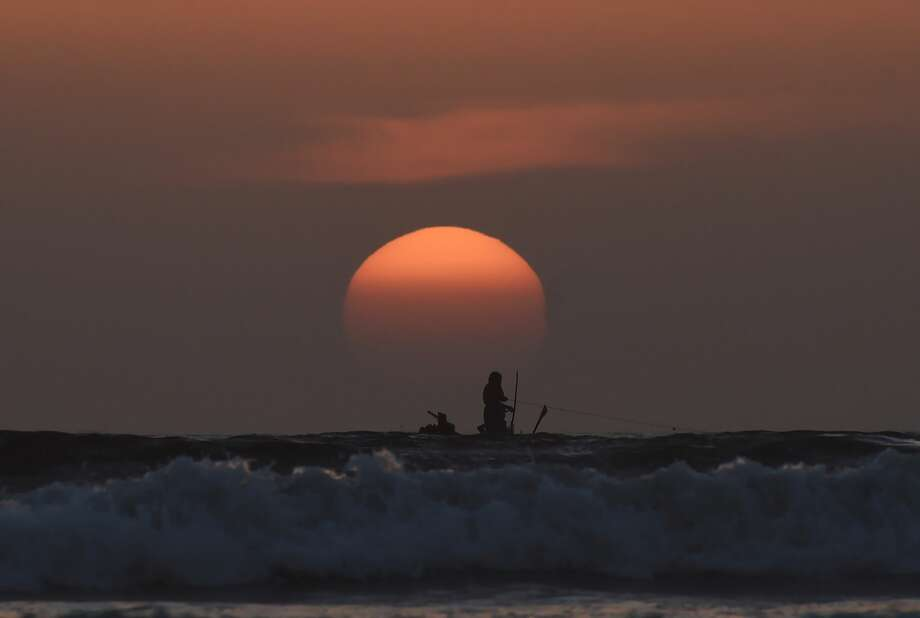 Pakistani fishermen work at sea during sunset near the port city of Karachi on December 31, 2017. Photo: ASIF HASSAN/AFP/Getty Images