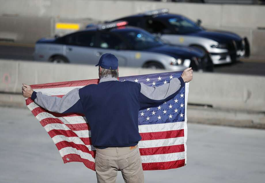 David Morgan of Highlands Ranch, Colo., holds a flag as a procession of law enforcement vehicles accompany a hearse carrying the body of a sheriff's deputy who was shot and killed on duty. Photo: David Zalubowski, Associated Press