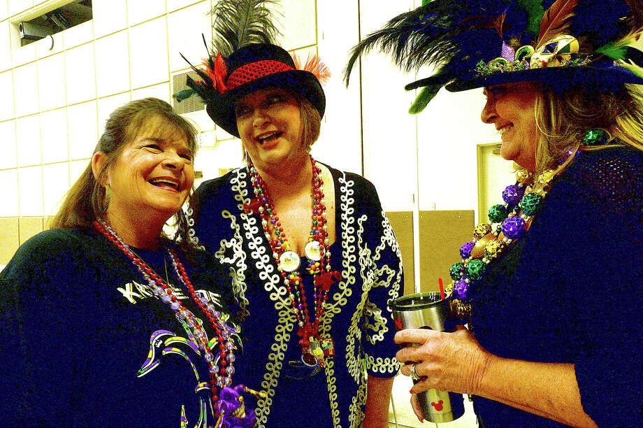From left, long-time friends Jerri McCown, JoJo James, and Debi Tamez joke with one another as they check out their Mardi Gras coin necklaces and enjoy the festivities at the fifth annual Beans and Jeans fundraising party held Saturday night at the Bob Bowers Civic Center in Port Arthur. The event coincides with Three Kings' Day, which officially ends the Christmas season and kicks off the start for Mardi Gras season. Revelers got in the spirit, celebrating with red beans and rice, king cake and musical entertainment by Electric Circus as the Krewes for this year's 25th Mardi Gras of Southeast Texas were introduced. The season reaches its climax with the weekend-long party and parades in downtown Port Arthur that begins February 23. Photo taken Saturday, January 7, 2017 Kim Brent/The Enterprise Photo: Kim Brent / Beaumont Enterprise
