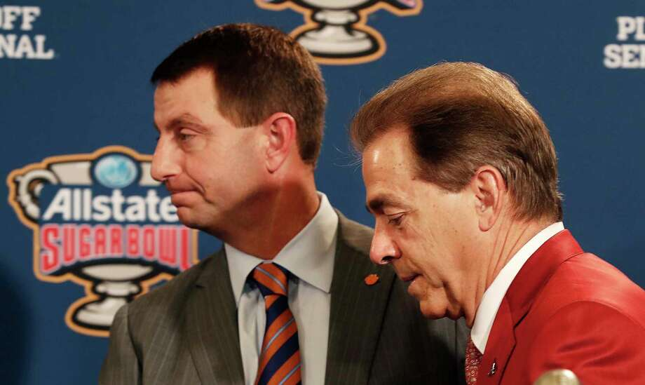 Clemson head coach Dabo Swinney and Alabama head coach Nick Saban, left, greet each other at a joint news conference with the Sugar Bowl trophy for their upcoming semi-final playoff game, for the NCAA football national championship, in New Orleans, Sunday, Dec. 31, 2017. (AP Photo/Gerald Herbert) Photo: Gerald Herbert, STF / Copyright 2017 The Associated Press. All rights reserved.