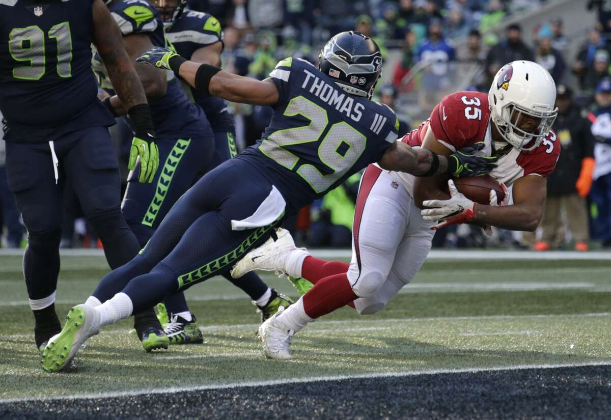 Arizona Cardinals running back Elijhaa Penny (35) dives past Seattle Seahawks free safety Earl Thomas (29) to score a touchdown in the first half of an NFL football game, Sunday, Dec. 31, 2017, in Seattle.