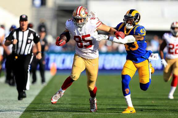 LOS ANGELES, CA - DECEMBER 31:  George Kittle #85 of the San Francisco 49ers eludes John Johnson #43 of the Los Angeles Rams on a pass play during the first half of a game  at Los Angeles Memorial Coliseum on December 31, 2017 in Los Angeles, California.  (Photo by Sean M. Haffey/Getty Images)
