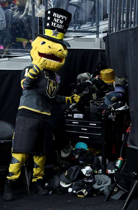Chance the Golden Gila Monster poses with hats collected after William Karlsson's third goal. Photo: Ethan Miller, Getty Images