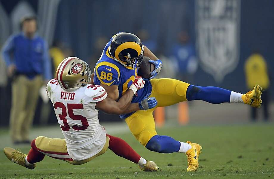 49ers safety Eric Reid (35) tackles Rams tight end Derek Carrier in Sunday's victory. Reid, a free agent, says teams may be reluctant to sign him because he kneels for the national anthem. Photo: Mark J. Terrill, Associated Press