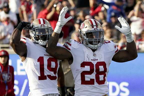 San Francisco 49ers running back Carlos Hyde, right, celebrates after scoring against the Los Angeles Rams during the first half of an NFL football game Sunday, Dec. 31, 2017, in Los Angeles. (AP Photo/Rick Scuteri)