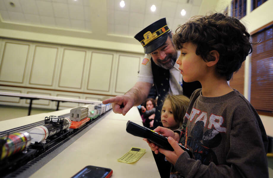Dennis Shore, of Flushing, NY, hands over the model train controls to Ashton Rubin, 5, and brother Leo, 3, of Westport, at the Dennis the Train Man exhibit at the Westport Senior Center, part of First Night 2018 festivities in Westport, Conn. on New Year's Eve, Sunday, December 31, 2017. Photo: Brian A. Pounds, Hearst Connecticut Media / Connecticut Post