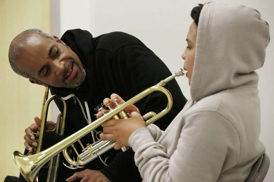 Above: Christopher Clarke, SFJazz teaching artist, mentors Camilo Garduno, 13, on the trumpet at Willie L. Brown Jr. Middle School. Left: Workbooks are part of the program to reach 23,000 middle school students. Photo: Lea Suzuki / Photos By Lea Suzuki / The Chronicle / ONLINE_YES