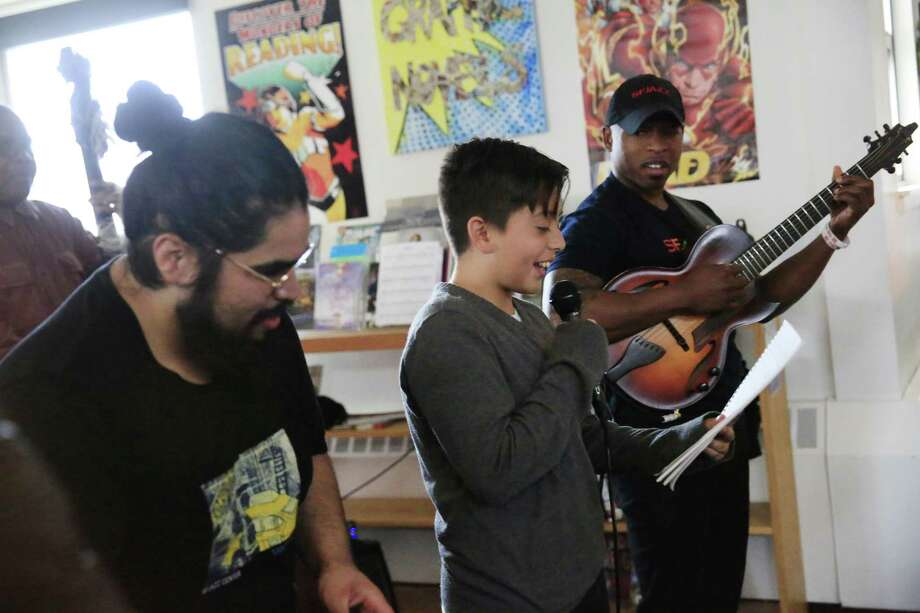 SFJazz's Jarvis Subia (left), poet mentor, and Terrence Brewer, teaching artist, listen as a Martin Luther Jr. Middle School sixth-grader performs his poem. Photo: Lea Suzuki / Lea Suzuki / The Chronicle / ONLINE_YES