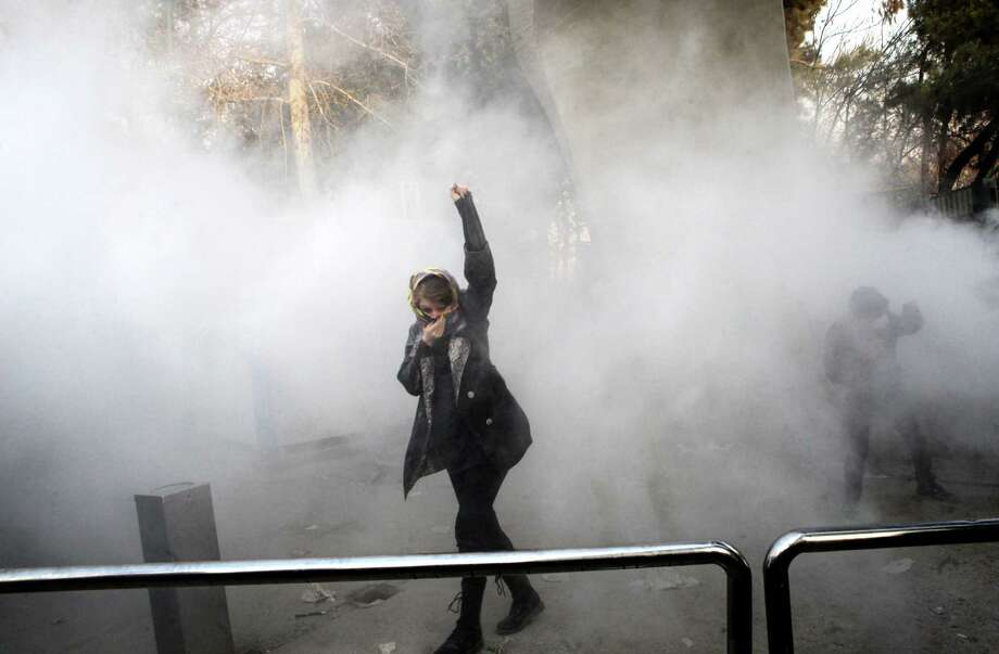 TOPSHOT - An Iranian woman raises her fist amid the smoke of tear gas at the University of Tehran during a protest driven by anger over economic problems, in the capital Tehran on December 30, 2017. Students protested in a third day of demonstrations sparked by anger over Iran's economic problems, videos on social media showed, but were outnumbered by counter-demonstrators. / AFP PHOTO / STR        (Photo credit should read STR/AFP/Getty Images) *** BESTPIX *** Photo: AFP Contributor#AFP / AFP
