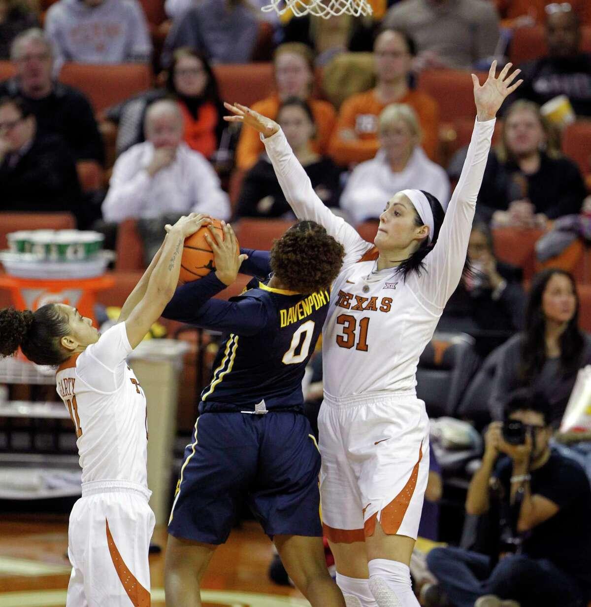 Texas' Brooke McCarty, left, blocks a shot by West Virginia's Naomi Davenport, center, with help from teammate Audrey-Ann Caron-Goudreau on Sunday.