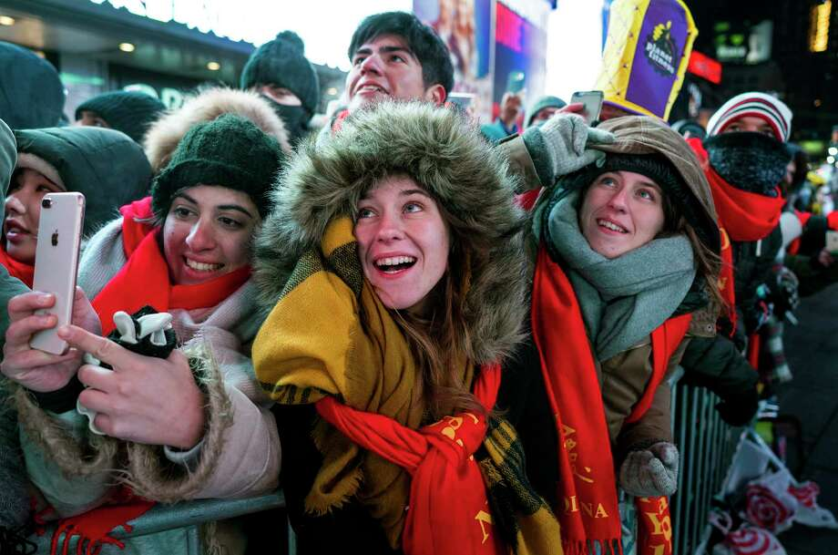 Revelers gathered on Times Square in New York watch the ceremonial ball rise to the top of a pole high above the street Sunday, Dec. 31, 2017, in preparation for the ball drop during New Year's Eve celebrations. (AP Photo/Craig Ruttle) Photo: Craig Ruttle / FR61802 AP