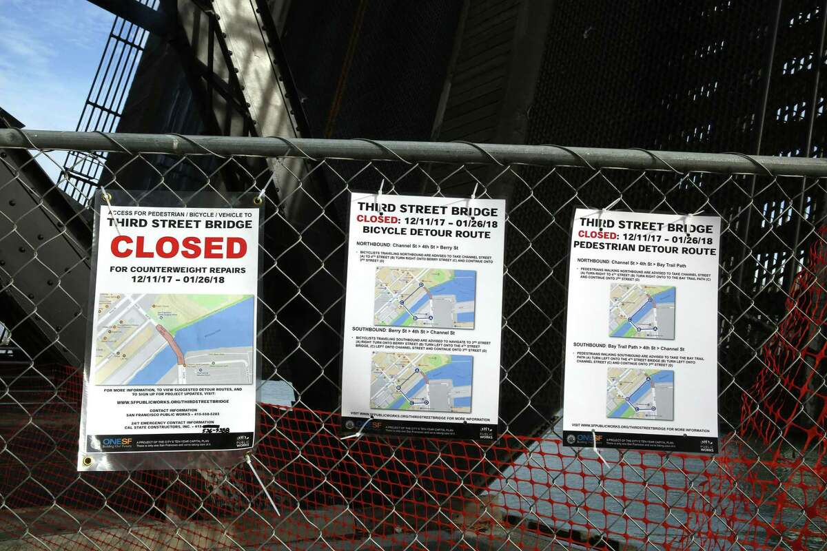 Signs at the Lefty O'Doul Bridge explain the drawbridge's closure for counterweight repairs and lay out alternate routes for cyclists and pedestrians.