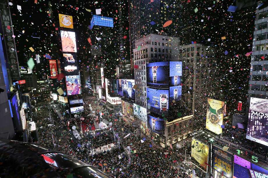 confetti drops over the crowd as the clock strikes midnight during the new years celebration in