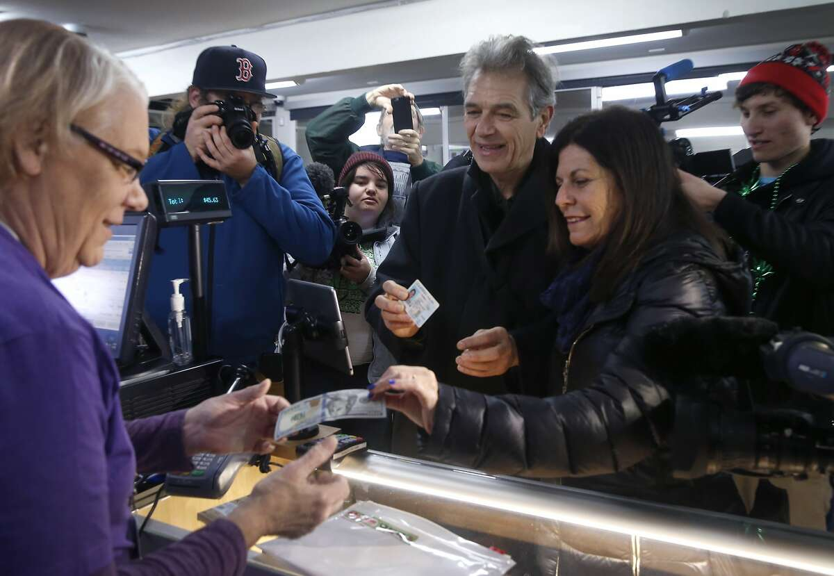 Chris Conrad and his wife Mikki Morris (right) are the first customers to purchase legalized marijuana at the Berkeley Patients Group dispensary on the first day of recreational cannabis sales in Berkeley, Calif. on Monday, Jan. 1, 2018. Assisting them with the transaction is Sue Gardea (left).