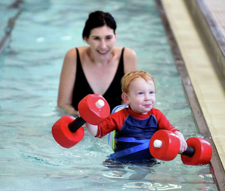 Betsy Barbieri plays with her son, Leo Hult, 2, in the pool at the JCC of Greater New Haven in Woodbridge during a New Year's Eve Beach Party on Sunday. They are visiting from Oregon. Photo: Arnold Gold / Hearst Connecticut Media / New Haven Register