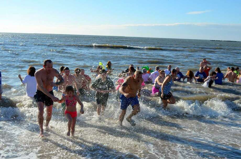 More than 200 people navigated 2-foot swells in 41-degree water during last year's 17th annual Icy Plunge for the Cure benefit for breast cancer research and education at Savin Rock Beach. This year's 2018 plunge is set for 9 a.m. Jan. 13 -- and will be followed by the first Spike for the Cure beach volleyball tournament, also a benefit for breast cancer, at 11 a.m. at Sea Bluff Beach. Photo: Contributed Photo / Michael P. Walsh, City Of West Haven