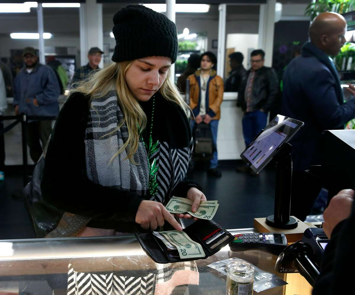 Tyler Hess, who recently relocated from Indiana, pays cash for marijuana products at the Berkeley Patients Group dispensary on the first day of legalized recreational cannabis sales in Berkeley, Calif. on Monday, Jan. 1, 2018.